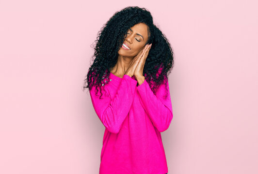 Middle age african american woman wearing casual clothes sleeping tired dreaming and posing with hands together while smiling with closed eyes.