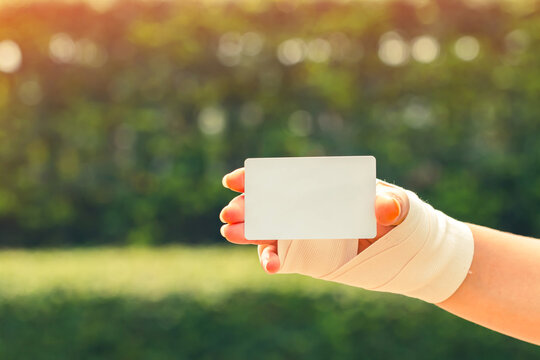 Patient woman with a bandage on her hand are holding and show a white card or credit on sunlight in the public park, Loan for health insurance concept.