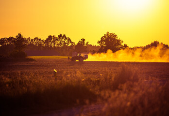 A harvester working on the field during the sunset hours in summer. Summertime scenery of Northern Europe.