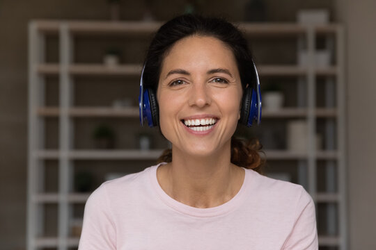 Smiling attractive millennial hispanic latin woman wearing wireless headphones looking at camera, holding pleasant video call zoom conversation, communicating distantly with client or partners.