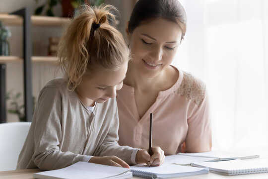 Out of school education. Helping young mom engaged in learning activity with preteen daughter assist in studying maths or english rules. Smiling millennial lady teacher give home lesson to little girl