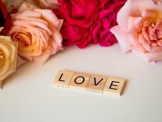 Fototapeta LOVE - napis z drewnianych kostek, róże w tle, różowy kolor obraz