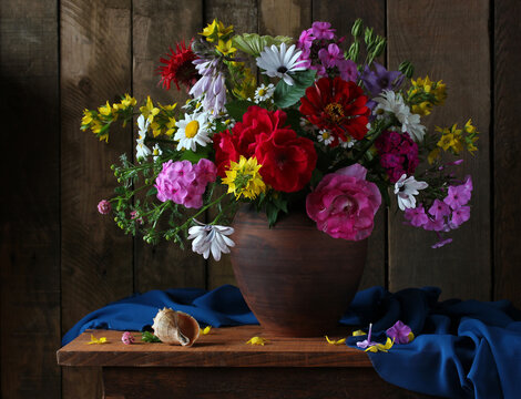 bouquet of garden flowers in a clay jug.