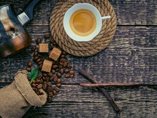 A cup of frothy coffee, a bag of spilled coffee beans and cane sugar lumps on an old wooden surface. Flat lay, vintage