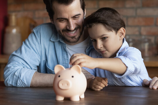Happy dad teaching smart little son to save and invest money, encourage kid for accounting, investment, planning future budget. Boy hugging father, dropping cash into piggy bank. Family economy