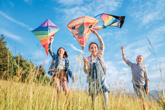 Smiling gils and brother boy running with flying colorful kites on the high grass meadow in the mountain fields. Happy childhood moments or outdoor time spending concept image.