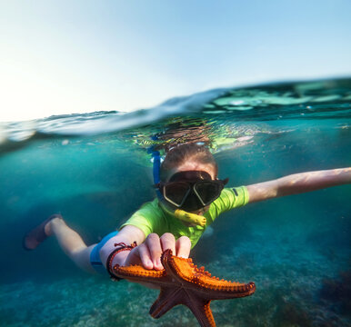 Underwater shot of a young teenage boy snorkeling with dive face mask in the blue Indian Ocean waves near the Zanzibar island with a big orange starfish in his hand. Exotic vacations concept image.