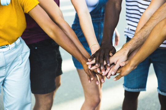 Close up multi ethnic group of young students stacking hands together - Millennial people celebrating together outdoor - College students teamwork stacking hand Concept