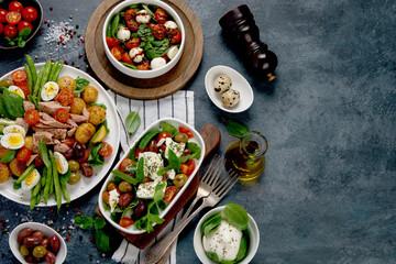 Fototapeta Assorted salads on dark gray background. Seasonal food concept. obraz