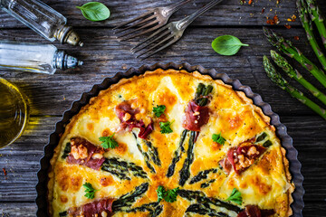 Tart with asparagus and serrano ham on wooden table