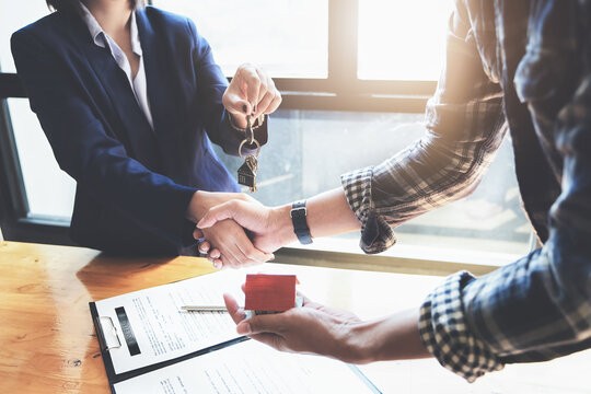 Focus on the congratulatory handshake. The real estate agent agrees to buy the home and hand the keys to the customer at the agent's office. conceptual agreement.