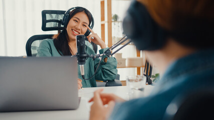 Asia girl radio host record podcast use microphone wear headphone interview celebrity guest content...