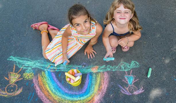 Children paint a rainbow on the asphalt. Selective focus.
