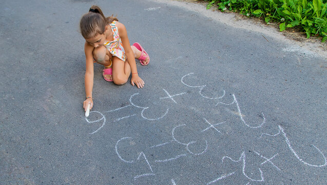 The child is doing chalk lessons on the asphalt. Selective focus.