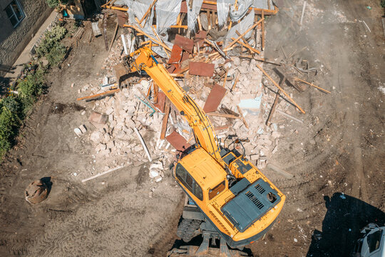 Hydraulic Excavator Breaks House. Building Demolition or Destruction for New Construction, aerial top view.