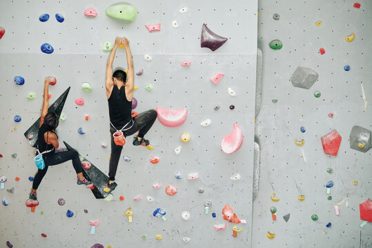 Young couple climbing up the wall when training for competition at indoor bouldering facility