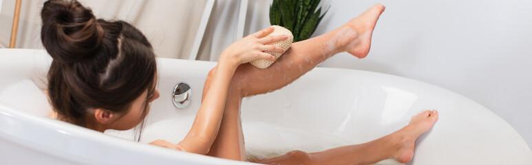 Fototapeta young woman with hair bun taking bath with loofah in bathtub, banner obraz
