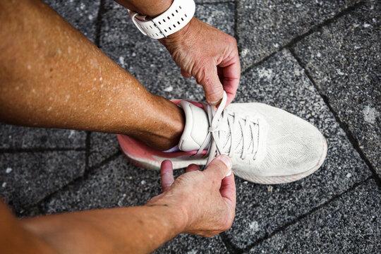 Closeup of hispanic hands tying sport shoe. Shot from above