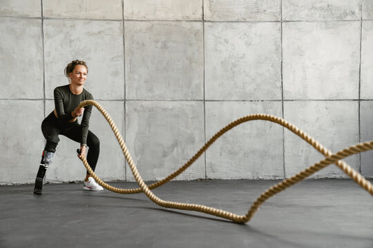 Young sportswoman with prosthesis working out with battle ropes