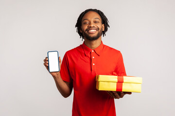 Fototapeta Smiling man with dreadlocks wearing red casual style T-shirt, holding gift box and cell phone with blank display for online shopping advertising. Indoor studio shot isolated on gray background. obraz