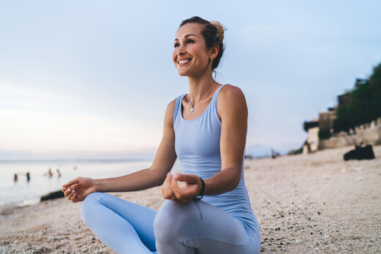 Cheerful Caucasian woman sitting in lotus pose and smiling enjoying free time for yoga practice at seashore, happy female 30s in tracksuit feeling good during morning for asanas at coastline