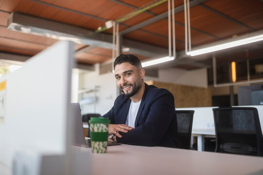 Smiling businessman on laptop in the office