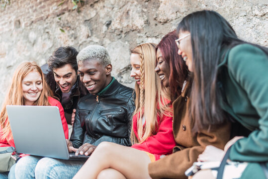 Group of multiracial friends gathering around laptop