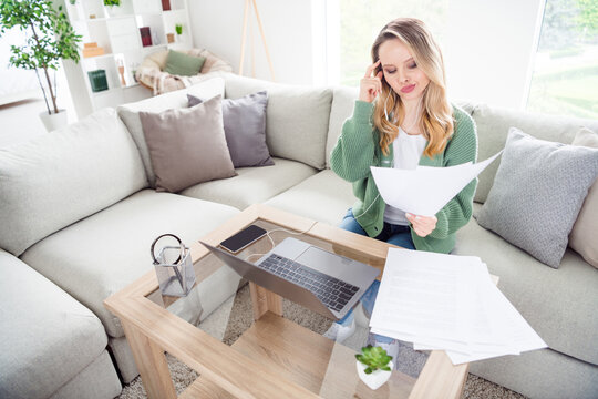 Portrait of attractive minded girl finance manager reading documents deciding development at home light white flat indoors