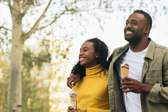 black couple eating ice cream in a park