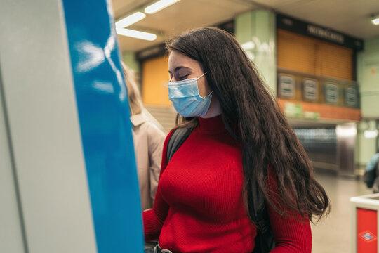 girls in mask buying ticket for metro