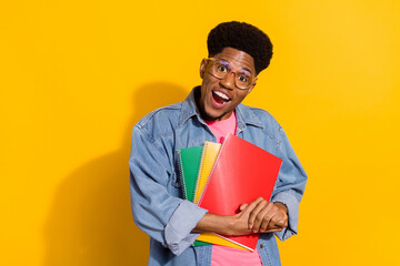 Photo of charming cheerful afro american young man hold hands notebooks isolated on yellow color background Wall mural