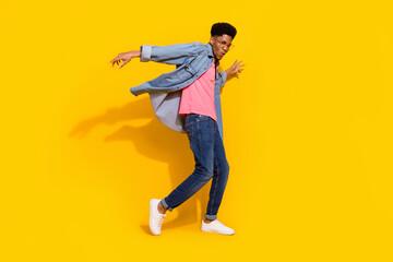 Fototapeta Full body photo of happy cheerful dark skin man fly wind shirt dancer isolated on bright yellow color background obraz