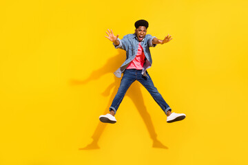 Full length photo of happy afro american young man jump up crazy mood isolated on yellow color background Wall mural