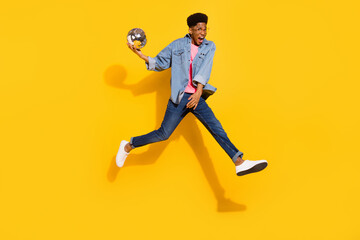 Full body photo of cheerful young afro american man jump up hold ball disco isolated on yellow color background Wall mural