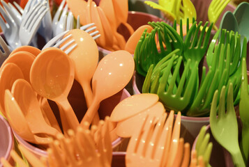 Fototapeta Closeup carrot orange and pear green colors plastic ware forks and spoons in plastic cups obraz