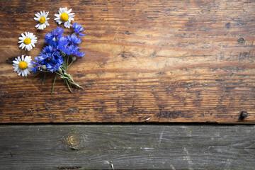 Obraz Kompozycja z kwiatów na tle drewnianych starych desek - fototapety do salonu