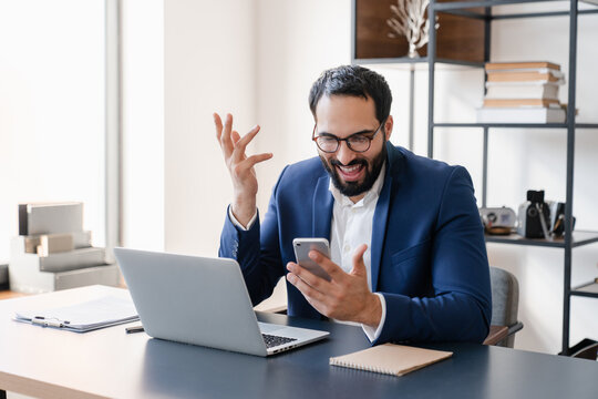 Extremely happy Middle Eastern businessman excited about his achievements using smart phone, getting promotion, salary, successful contract deal. Remote working office at home