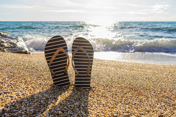 Fototapeta Flip-flops on sea beach against sunny seascape. Flip flops slippers in nautical style in small stones at seaside. Beautiful view of sea shore in summer day. Summer beach vacation, weekend trip obraz