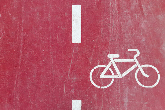 Red bike path is marked with a white painted bicycle sign, top view.