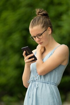 Teen girl with a mobile phone in the park.