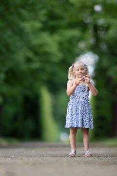 Little blond girl in the park portrait.