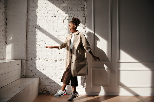 Black woman in trench coat dancing under sunlight. Full length view of pretty african american girl jumping near bricked wall.