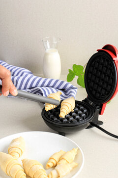 Woman Hand Put Frozen Waffle to Electric Mini Waffle Maker using Grey Tongs. Making Homemade Croissant Waffle (Croffle) for Breakfast.