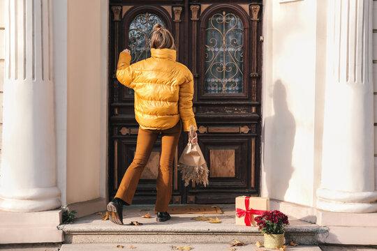 Woman knocking on door of house on autumn day