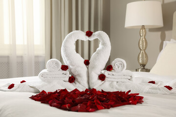 Obraz Beautiful swans made of towels and red rose petals on bed in room - fototapety do salonu
