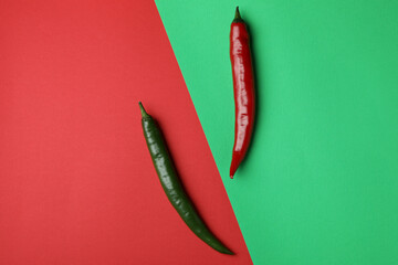 Red and green hot chili peppers on two tone background