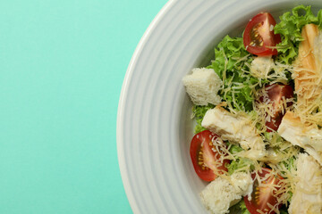 Plate with Caesar salad on mint background
