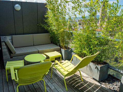 Terrasse mit Holzdeck und einem Ruhebereich mit grünen Möbeln und Bambus in Zinkgefäßen
