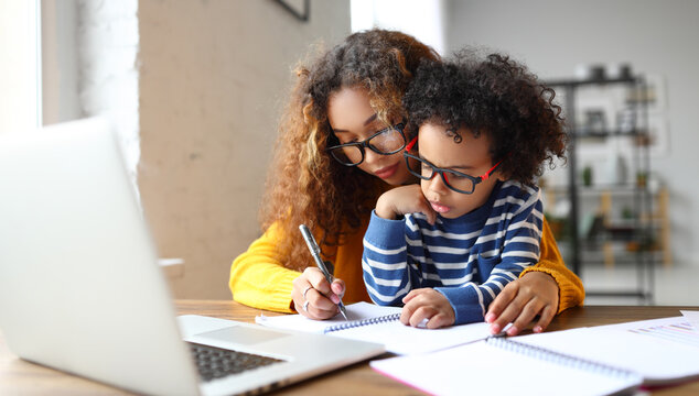 African mom taking care of little son, sitting together at desk and learning to write