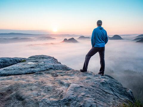 Hiker watch misty melancholic morning in cloudscape.